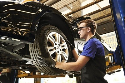 Male Goodyear technician completing a tire rotation