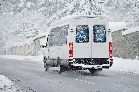 White cargo van driving down snowy road